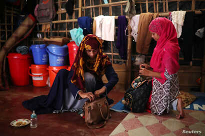 Formin Akter packs her bag next to her friend Shahima before heading to Chittagong, Bangladesh, Aug. 24, 2018.