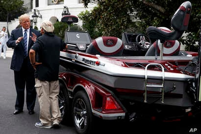 """President Donald Trump talks with Jimmy Houston of Ranger Boats as he participates in a tour during a """"Made in America Product Showcase"""" at the White House, July 23, 2018."""