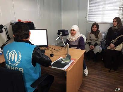 FILE - Biometric identification systems are being used in novel ways. In this photo, a Syrian refugee girl poses for a biometric iris scan in an interview room of the U.N. refugee agency in Amman, an intial step in her efforts to be approved for rese...