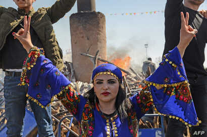 A young woman flashes the victory sign in front of a bonfire as Turkish Kurds gather during Newroz celebrations for the new year in Diyarbakir, southeastern Turkey, on March 21, 2018.
