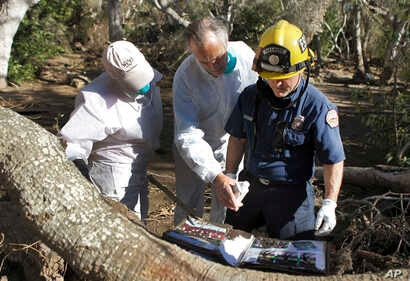 Paige Beard, from left, Curtis Skene and Montecito Fire Paramedic Kurt Hickman try to identify a photo album found in the debris near East Valley Road in Montecito, Calif., Jan. 25, 2018. Skene fought back tears as firefighters uncovered old photogra...