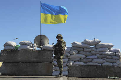 FILE - A Ukrainian serviceman stands guard at a checkpoint near the town of Armyansk in Kherson region adjacent to Crimea, March 21, 2014.