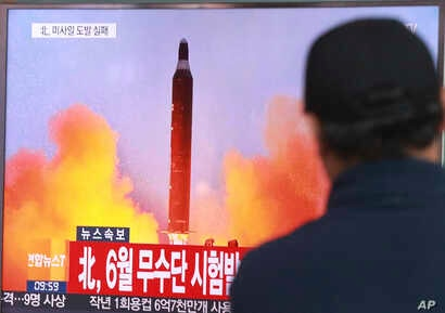 """FILE - A man watches a TV news program, Oct. 16, 2016, showing a file image of a missile launch conducted by North Korea. The letters read """"North attempted to fire a mid-range Musudan missile in June."""""""