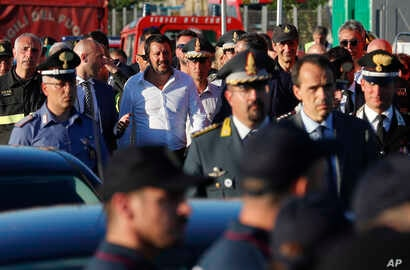 Interior Minister Matteo Salvini, center, arrives at the site where the Morandi highway bridge collapsed, in Genoa, northern Italy, Aug. 15, 2018.