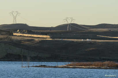 Dakota Access Pipeline equipment is seen near Lake Oahe, near the Standing Rock Indian Reservation, in this picture taken from across the Missouri River in Linton, North Dakota, Nov. 9, 2016.