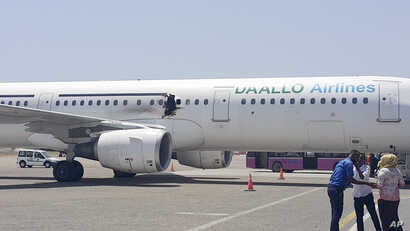 In this photo taken Feb. 2, 2016, a hole is seen in a plane operated by Daallo Airlines as it sits on the runway of the airport in Mogadishu, Somalia.