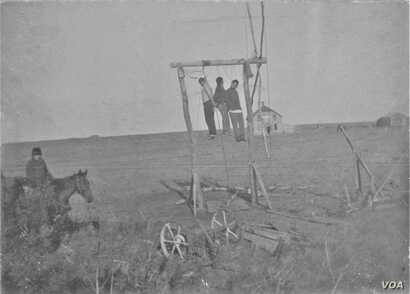 This grim photo shows three Native American men, Paul Holytrack, Alex Cadotte and Philip Ireland, who were lynched for their suspected role in the murder of a white family. Courtesy: State Historical Society of North Dakota, Emmons County Historical ...