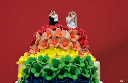 A wedding cake in rainbow colors and decorated with figurines of two women and two men is pictured in Berlin, June 30, 2017.