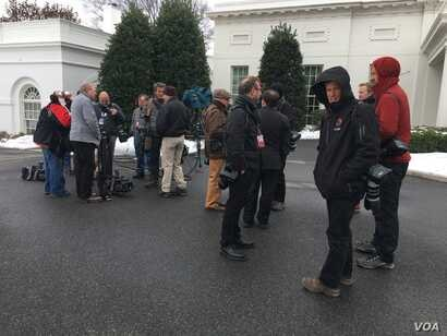 Members of a White House press pool waiting outside the West Wing on a chilly day.