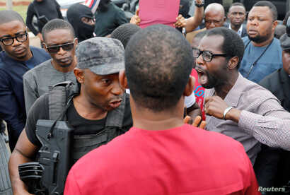 A man reacts next to a member of security forces at the entrance of the National Assembly in Abuja, Nigeria, Aug. 7, 2018.