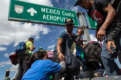 U.S.-bound Central American migrants get on to a truck for a a free ride, as part of a thousands-strong caravan moving through Puebla, Mexico, Nov. 5, 2018.