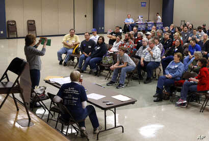 Voters listen to instructions during a Democratic party caucus in Nevada, Iowa, Feb. 1, 2016.