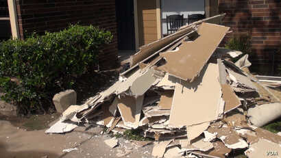 In some parts of Houston, there are piles of broken drywall outside apartment doors, as well as carpets and warped wood from floors and doorways. (G. Flakus/VOA)