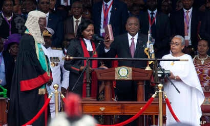 Kenyan President Uhuru Kenyatta, center, is sworn-in accompanied by his wife Margaret, right, and during his inauguration ceremony at Kasarani stadium in Nairobi, Kenya, Nov. 28, 2017.
