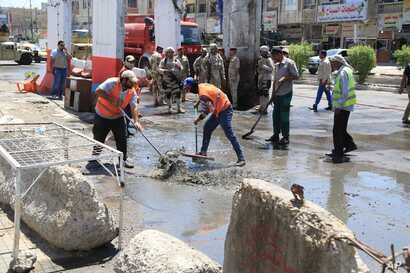 Municipality workers clean up debris in the aftermath of a bomb attack in Baghdad northern Shaab district, Iraq, May 30, 2016.