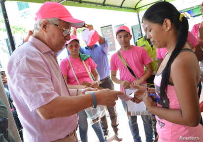 Soledad's Mayor Joao Herrera (L)  gives a woman, condoms and kits with insect repellent during a campaign to fight the spread of Zika virus in Soledad municipality near Barranquilla, Colombia, in this Feb. 1, 2016 handout photo supplied by the Soleda...