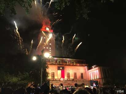Two commencement traditions at the University of Texas at Austin: lighting up the top of the campus landmark tower in orange - the official color of the university - and fireworks at the end of the ceremony. (C. Presutti/VOA)
