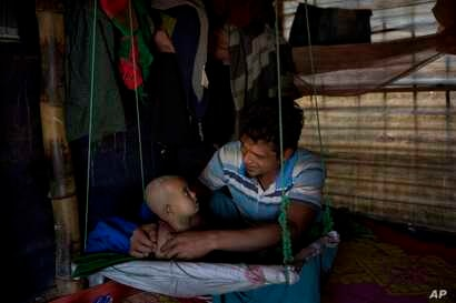 In this Jan. 21, 2018 photo, Rohingya Muslim refugee Noor Kadir, 24, from the Myanmar village of Gu Dar Pyin, plays with his son inside the family makeshift shelter in Balukhali refugee camp, Bangladesh. The Associated Press has confirmed more than f...