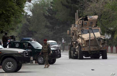 A damaged US military vehicle is being pulled near the site of a suicide attack in Kabul, Afghanistan, May 3 , 2017. Afghan officials say that at least four people have been killed in a suicide car bomb attack in the capital Kabul.