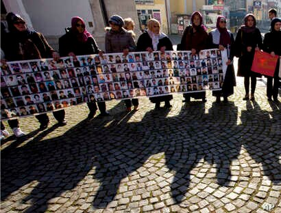 FILE - Members of the Srebrenica Women Union hold photographs of the 1995 Srebrenica massacre dead and missing in Tuzla, Bosnia, Nov. 11, 2017. The Balkan nations that fought bitter wars as the former Yugoslavia crumbled in the 1990s signed an agreem...
