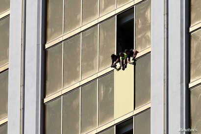FILE: Workers board up a broken window at the Mandalay Bay hotel, where shooter Stephen Paddock conducted his mass shooting along the Las Vegas Strip, in Las Vegas, Nevada, U.S., Oct. 6, 2017.
