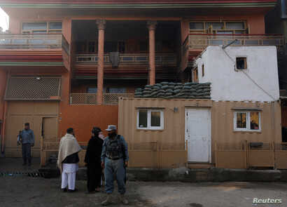 Afghan policemen keep watch outside the house of an Afghan member of parliament that was attacked by Taliban, Dec. 21, 2016, in Kabul, Afghanistan.
