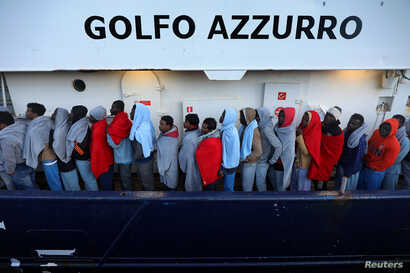 FILE - Migrants line up as they wait to be processed by Italian authorities aboard the former fishing trawler Golfo Azzurro moored in the port of Augusta following their rescue by Spanish NGO Proactiva Open Arms from their drifting dinghies off the L...