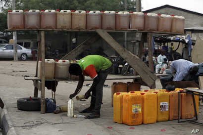 A man sells fuel on the road side in Kano, Nigeria, April 1, 2016. Nigeria's oil minister apologized this week for a fuel shortage that has created long lines at gas stations and left travelers stranded on highways in sub-Saharan Africa's top oil pro...