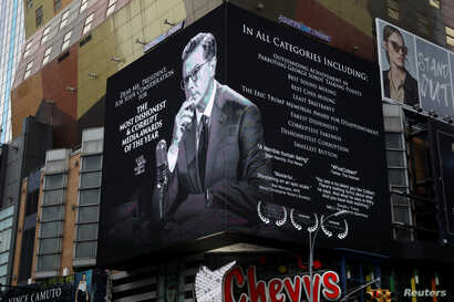 """A billboard late-night talk show host Stephen Colbert is seen near New York's Times Square, January 16, 2018.  Colbert is jokingly campaigning for President Trump's """"fake news awards."""""""