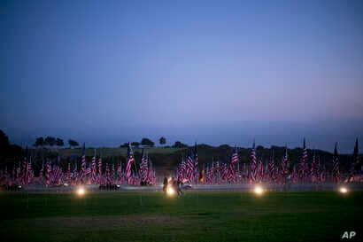 Visitors walk around the Pepperdine University's annual display of flags honoring the victims of the 9/11 terrorist attacks, Monday, Sept. 10, 2018, in Malibu, Calif.
