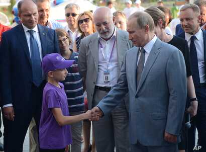 FILE - Russian President Vladimir Putin, right, shakes hands with a boy as he visits the Sirius college for gifted children in the Black Sea resort of Sochi, Russia, Sept. 1, 2015. In center is Russian Renova's CEO Viktor Vekselberg.
