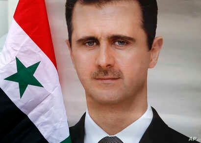 FILE - A man holds a Syrian national flag and a picture of Syrian President Bashar al-Assad during a protest outside the Syrian embassy in Belgrade, Serbia, April 15, 2018.