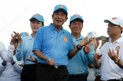 Cambodian Prime Minister Hun Sen, center, dances with his supporters during his Cambodian People's Party's last campaign for the July 29 general election, in Phnom Penh, Cambodia, July 27, 2018.