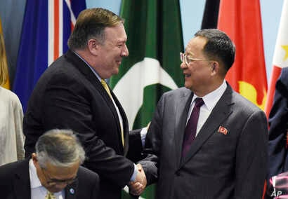 U.S. Secretary of State Mike Pompeo, left, greets North Korea's Foreign Minister Ri Yong Ho as they prepare for a group photo at the 25th ASEAN Regional Forum Retreat in Singapore, Aug. 4, 2018. Asia's top diplomats pressed North Korea on Saturday to...