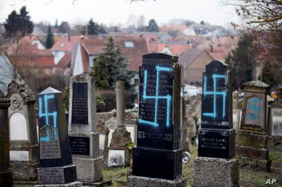 Vandalized tombs with tagged swastikas are pictured in the Jewish cemetery of Quatzenheim, eastern France, Tuesday, Feb.19, 2019.