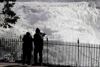 Ice is seen on the side of the Great Falls National Historic Park as a couple takes in the sights during a frigid winter day in Paterson, N.J., Jan. 30, 2019.