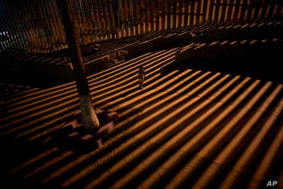 A boy plays as floodlights from the United States filter through the border wall, Jan. 11, 2019, in Tijuana, Mexico. The partial U.S. government shutdown has now become the longest closure in U.S. history as President Donald Trump and nervous lawmake...