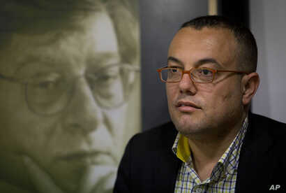 FILE - Palestinian novelist Atef Abu Saif attends a workshop in the West Bank city of Ramallah, March 1, 2015.