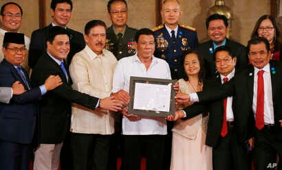 "FILE - President Rodrigo Duterte, center, and leaders of the Moro Islamic Liberation Front, including Al Haj Murad Ebrahim, left, Mohagher Iqbal, right, and Ghadzali Jaafar, second from right, hold together the signed ""Organic Law for the Bangsamoro"