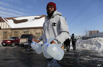 FILE - Lemott Thomas carries free water being distributed at the Lincoln Park United Methodist Church in Flint, Mich., Feb. 3, 2015.