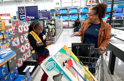 """Fast Checkout-Holiday: FILE - In this Nov. 9, 2018, file photo, Walmart associate Shanay Bishop, left, checks out customer Carolyn Sarpy on the sales floor as part of the """"Check Out With Me"""" program at a Walmart Supercenter in Houston."""