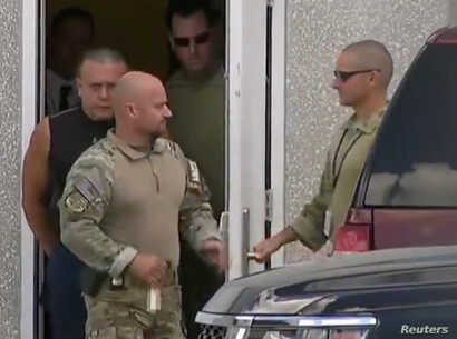 Cesar Altieri Sayoc (in dark shirt), who was arrested during an investigation into a series of parcel bombs, is escorted from an FBI facility in Miramar, Fla., Oct. 26, 2018, in this still image from video.