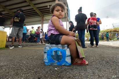 Kerialys Aldea de Jesus sits on bottled water at the Jose de Diego Elementary School where residents file FEMA forms for federal aid in the aftermath of Hurricane Maria in Las Piedras, Puerto Rico, Oct. 2, 2017.