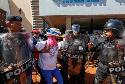 """A masked anti-government protester is arrested by police as security forces disrupt an opposition march, coined """"United for Freedom,"""" in Managua, Nicaragua, Sunday, Oct. 14, 2018."""