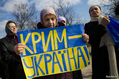 An ethnic Tatar women attends a pro-Ukraine rally denouncing the referendum on the future of the Crimean peninsula, in Simferopol, March 14, 2014.