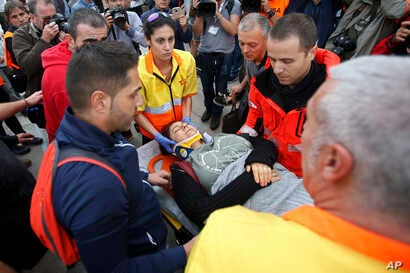 A woman is taken away on a stretcher after civil guards cleared would-be voters at the entrance of a sports center, assigned to be a referendum polling station by the Catalan government in Sant Julia de Ramis, near Girona, Spain, Oct. 1, 2017.