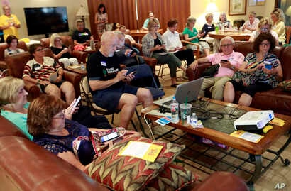 FILE - Community activists learn how to register voters on their phones at a democratic Stand Indivisible AZ monthly meeting in Scottsdale, Ariz., as they strategize about upcoming mid term elections, July 16, 2018.