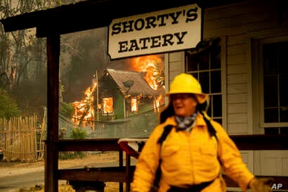 California State Parks Superintendent Lori Martin keeps watch on historic buildings as the Carr Fire burns a residence in Shasta, Calif.,  July 26, 2018.