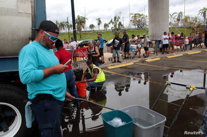 Local residents wait in line during a water distribution in Bayamon following damage caused by Hurricane Maria in Carolina, Puerto Rico, Sept. 30, 2017.