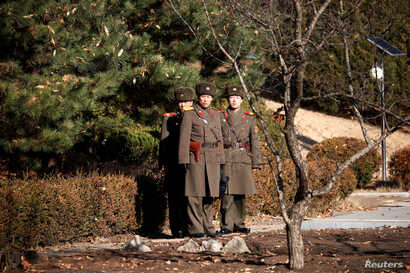North Korean soldiers keep watch toward the south next to where a North Korean defected on Nov. 13, 2017, at Panmunjom inside the demilitarized zone, South Korea, Nov. 27, 2017.